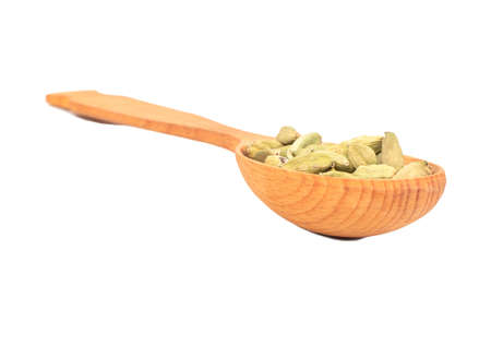 Large wooden spoon with dry cardamom isolated on white background Фото со стока