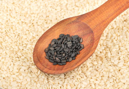 Black sesame in a wooden spoon on a background of white grains 写真素材 - 132049094