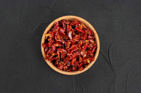Wooden bowl with pieces of dry red pepper on a dark background, top view Banco de Imagens