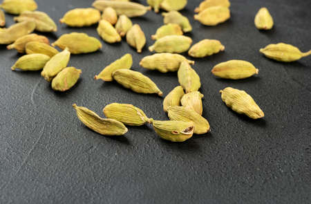 Scattered dry cardamom on a dark background