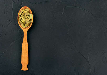 Green cardamom in wooden spoon on dark background, top view