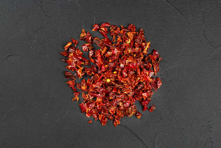 Pile of pieces of dry red pepper on a concrete background, top view Banco de Imagens