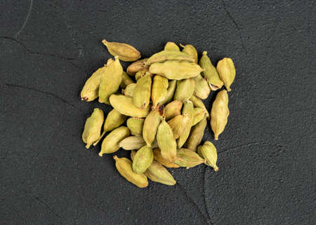 Pile of dry cardamom on dark concrete background, top view