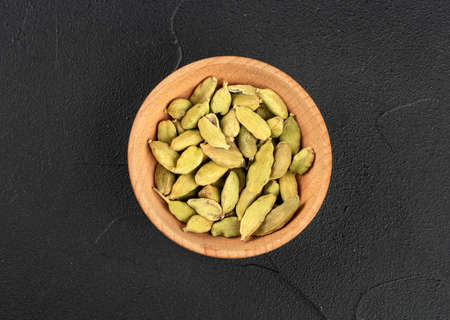 Dry cardamom in a wooden bowl on a concrete background, top view