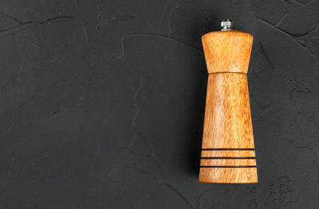 Wooden pepper pot on dark concrete background, top view