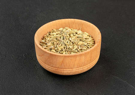 Dry fennel in a wooden bowl on a dark background Banco de Imagens