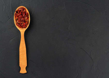 Pieces of dry red pepper in a spoon on an empty dark background, top view Banco de Imagens