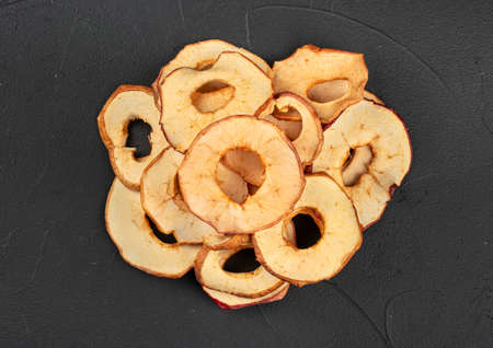 Pile of dry Apple chips on a dark background, top view