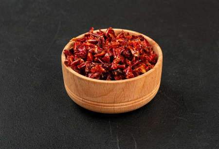 Wooden bowl with pieces of dry red pepper on a dark background