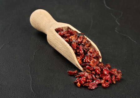 Dry barberry in a wooden scoop on a concrete background