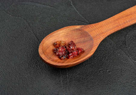 Small spoon with dry barberry on dark background closeup