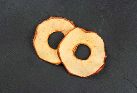 Two dry Apple chips on a dark concrete background, top view