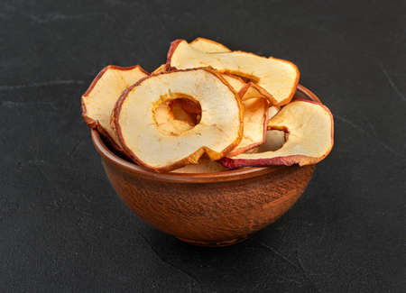Apple chips in a ceramic bowl on a concrete background