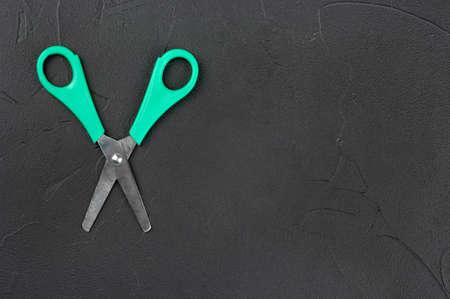 Scissors with plastic handle on empty dark background, top view 스톡 콘텐츠