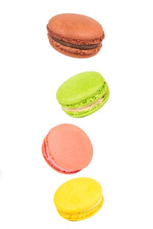 Four multicolored macaroons floating in the air on a white background 写真素材