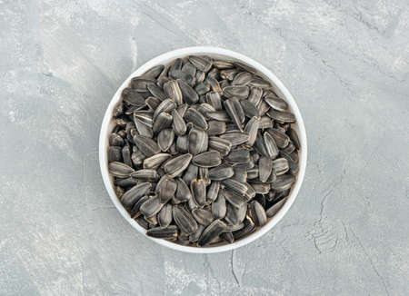 Ceramic bowl with sunflower seeds on a concrete background, top view 写真素材