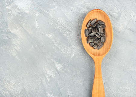 Sunflower seeds in a wooden spoon on an empty concrete background 写真素材