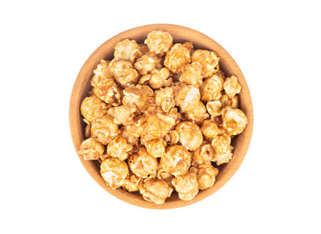 Caramel popcorn in wooden bowl isolated on white background, top view