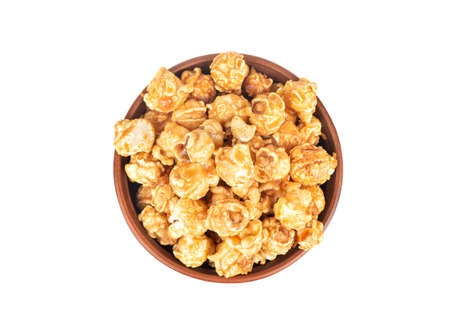 Ceramic bowl with caramel popcorn isolated on white background, top view