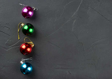 Four colorful Christmas balls on an empty concrete background