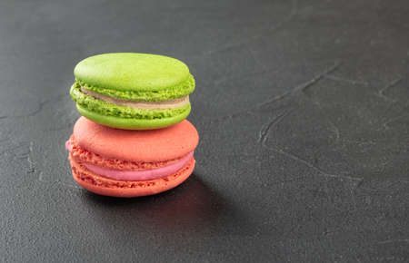 Pink and green macaroons on a dark concrete background