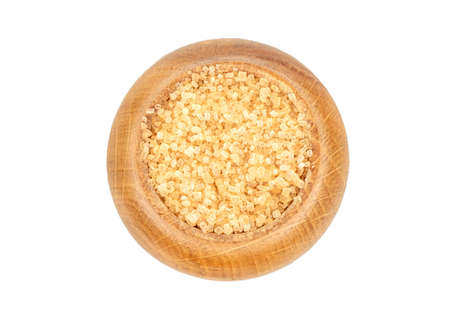 Brown sugar in a wooden container isolated on a white background, top view