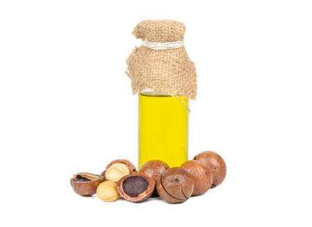Macadamia nuts with oil in a bottle on a white background Фото со стока