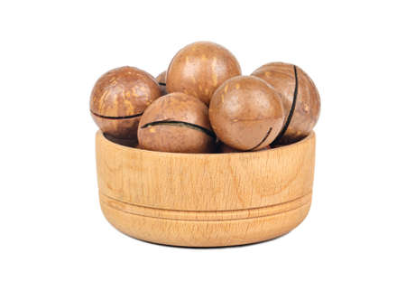 Macadamia nuts in a shell in a small wooden bowl on a white background Фото со стока