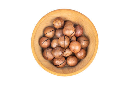 Macadamia nuts in a shell in a wooden bowl on a white background top view