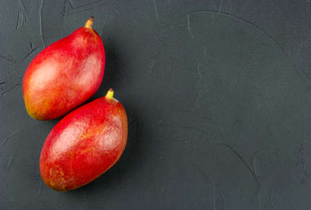 Two red delicious mango fruits on a concrete background, top view Фото со стока