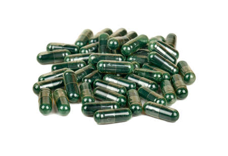 Pile of green capsules with medicinal herbs on a white background
