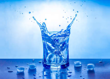 Ice splashing in a cool glass of water. Stock Photo