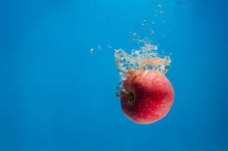 circular blue water ripple: Red apple in the water with a splash on a blue background