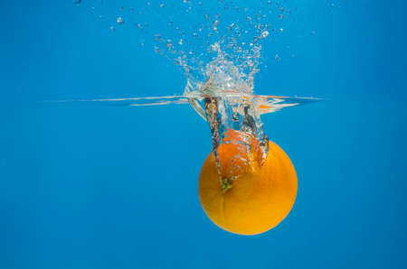 Orange splashing in water with blue background.