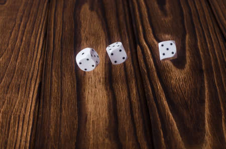 White dices on a wooden table.
