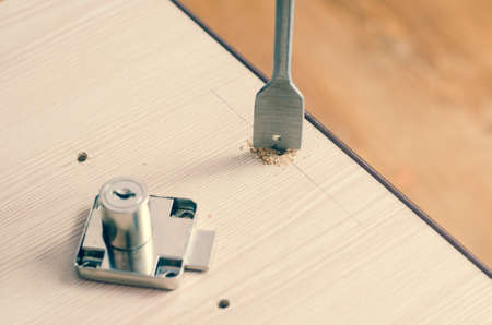 Drilling holes in a wooden block. Stock Photo