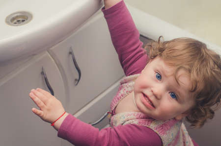 Little girl reaches for the sink in the bathroom. Stock Photo