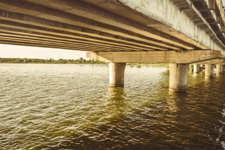 Old concrete bridge over the river. Stock Photo