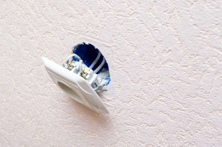 Old broken electrical socket fell out of wall.