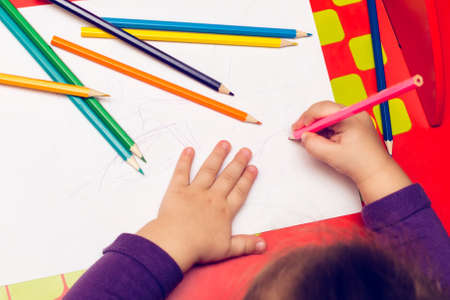 On the red table, children's hands with colored pencils and a blank sheet of paper.