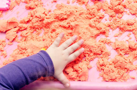 The hands of a child playing with kinetic sand. Stock Photo