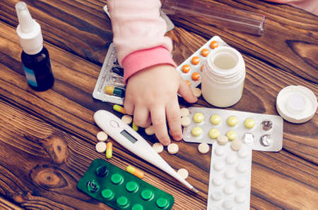 Childrens hands with medicines on a wooden table. A small child left unattended plays dangerous drugs.