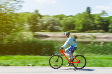A cyclist in a helmet rides a bicycle path, motion blur.
