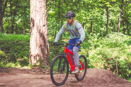 Cyclist in helmet on an orange bike doing a trick in a springboard jump in the forest, motion blur.