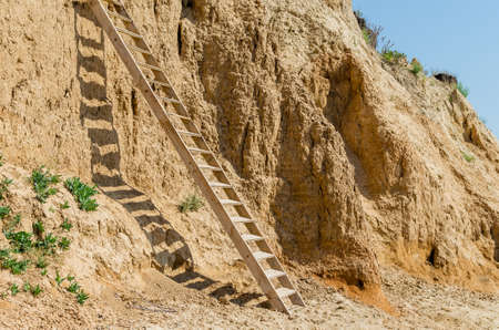 Wooden staircase attached to a clay rock on a sunny day. Stockfoto