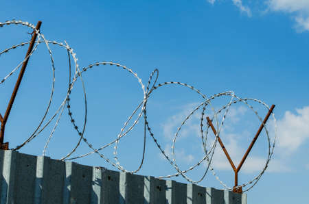 Metal fence with barbed wire on blue sky background. 스톡 콘텐츠