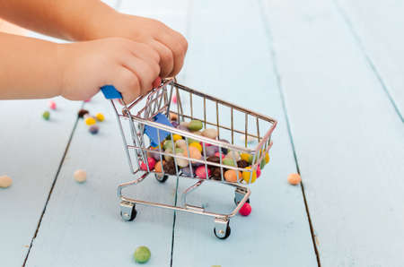 Hands of a child holding a shopping cart with colored sweets on a blue background.