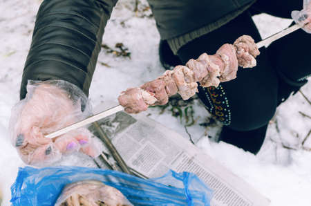 Women's hands strung meat on a skewer in the winter forest. Imagens