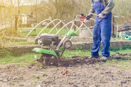 Man working in the spring garden with tiller machine.