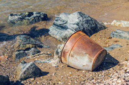 Old rusty bucket on a sandy beach. 免版税图像